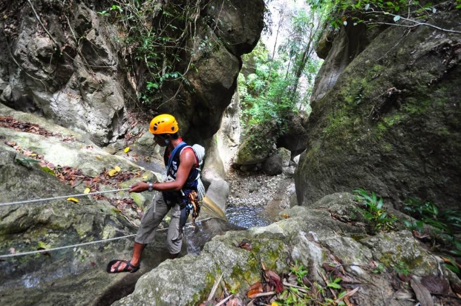 An adrenaline junkie rappels carefully down the canyons of MoalBoal